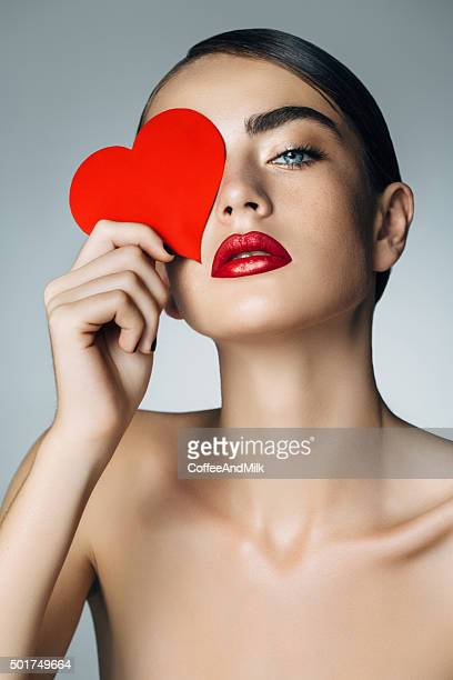 Studio shot of young beautiful woman holding artificial heart