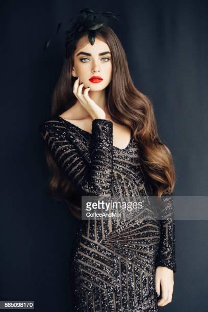 studio shot of young beautiful woman on light background - vestito nero foto e immagini stock