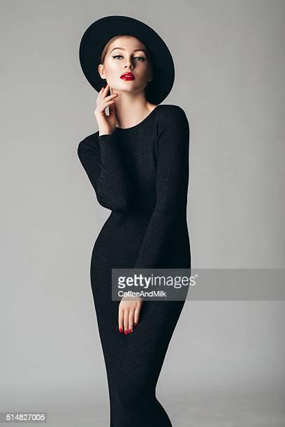 Studio shot of young beautiful woman wearing retro hat