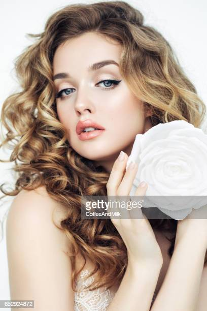Studio shot of young beautiful woman with flowers