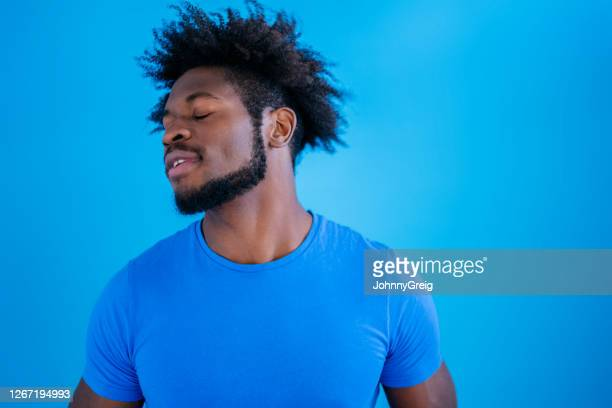 studio shot of young black man looking away with eyes closed - royal blue stock pictures, royalty-free photos & images