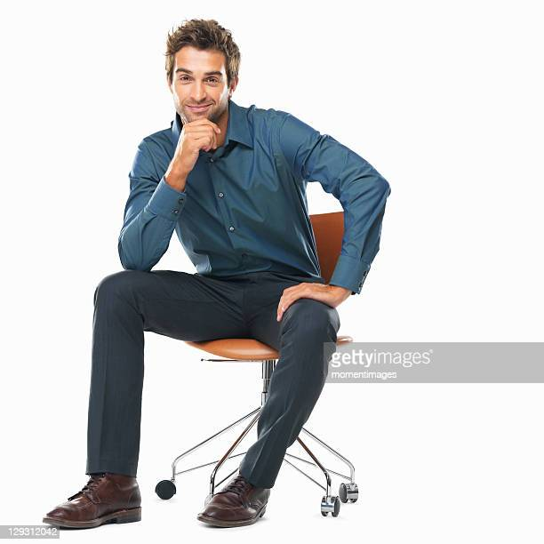 studio shot of young business man sitting on chair with hand on chin and smiling - mano en la barbilla fotografías e imágenes de stock
