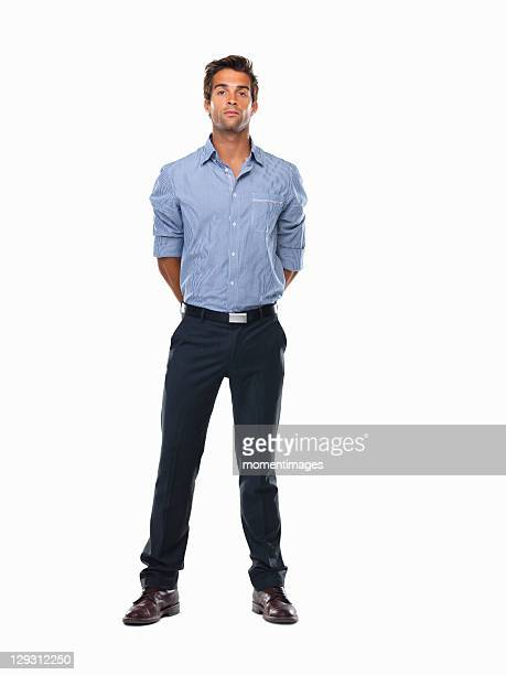 Studio shot of young business man standing with hands behind back