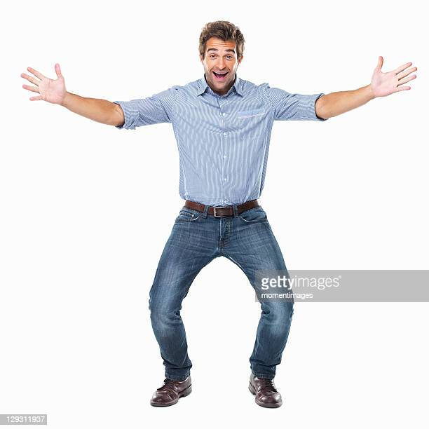 studio shot of young cheerful man with arms outstretched - human arm stockfoto's en -beelden