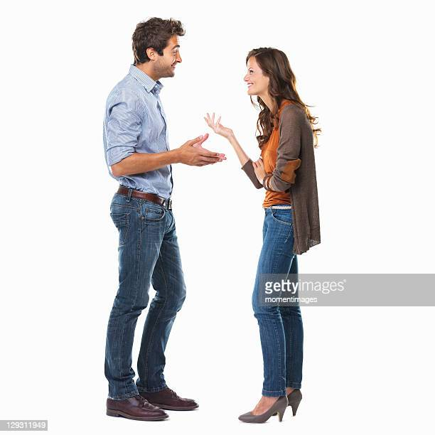 studio shot of young couple having conversation - cara a cara imagens e fotografias de stock