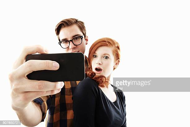Studio shot of young couple posing for selfie on smartphone