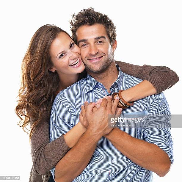 Studio shot of young couple smiling and embracing