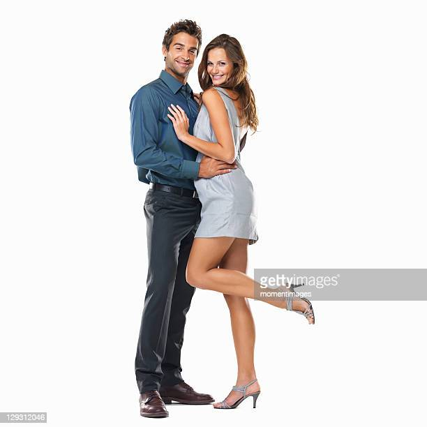 Studio shot of young couple standing together and smiling