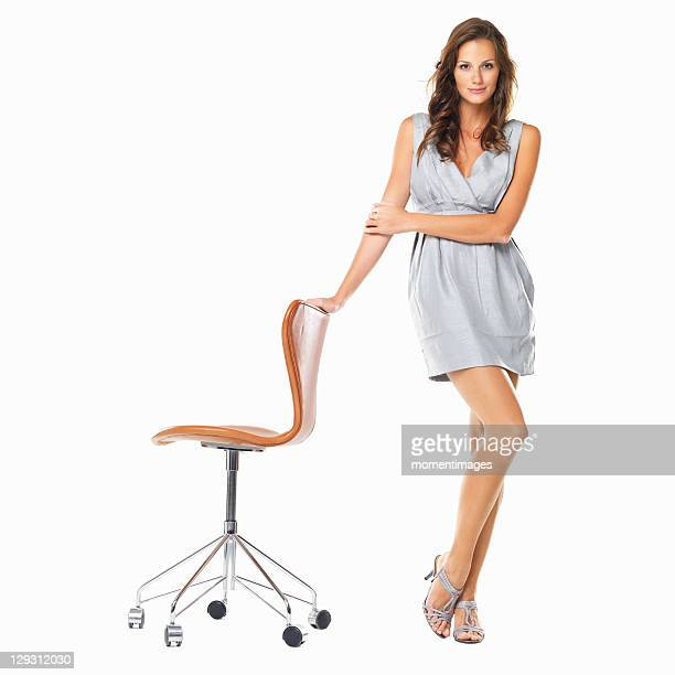 Studio shot of young elegant woman standing with hand on chair and smiling