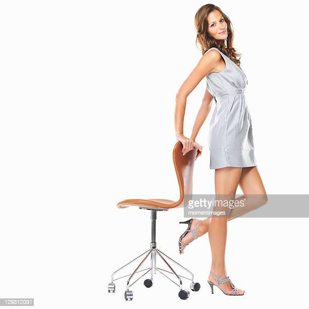 Studio shot of young elegant woman standing with hands on chair and smiling