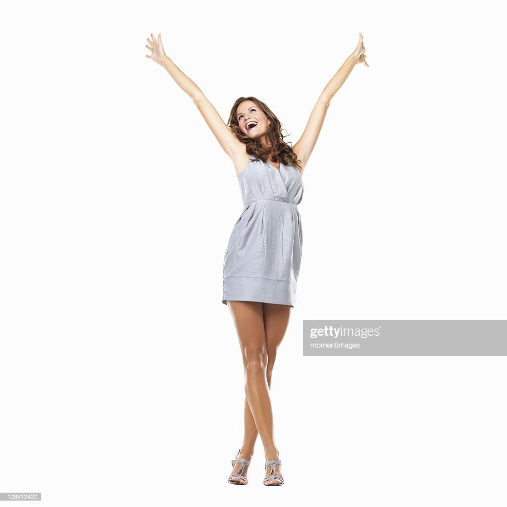 Studio shot of young excited woman celebrating success with hands raised : Stock Photo