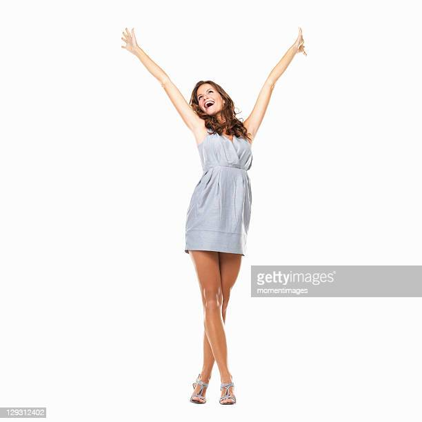 Studio shot of young excited woman celebrating success with hands raised