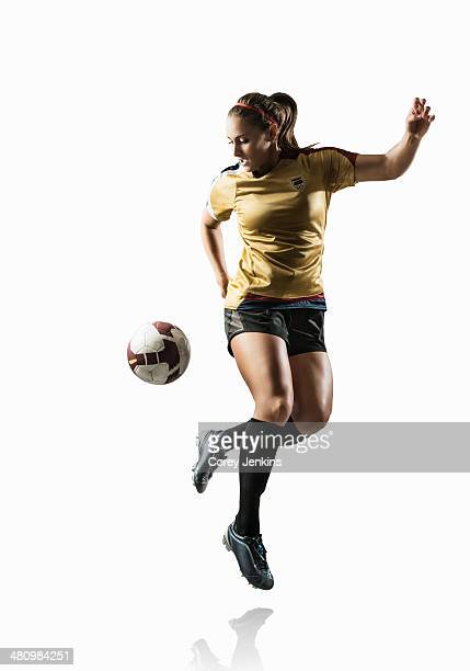 Studio shot of young female soccer player back kicking ball