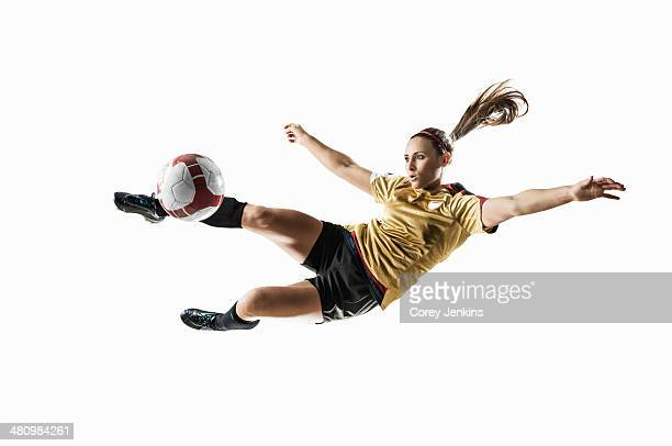 studio shot of young female soccer player kicking ball mid air - fußballspieler stock-fotos und bilder