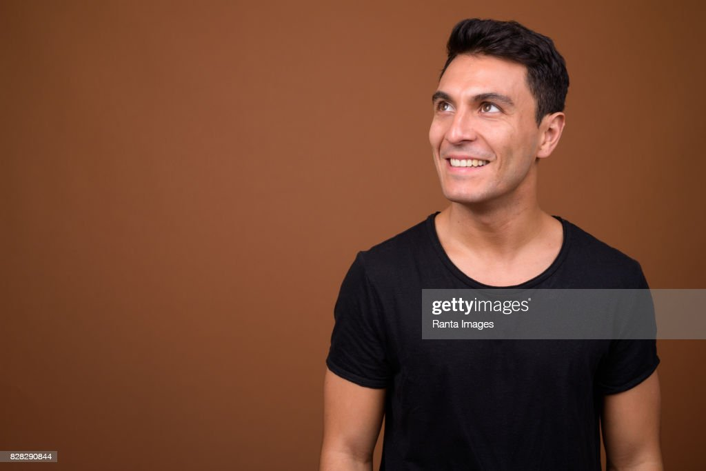 2be066522 Studio shot of young handsome Hispanic man wearing black shirt against  colored background : Stock Photo
