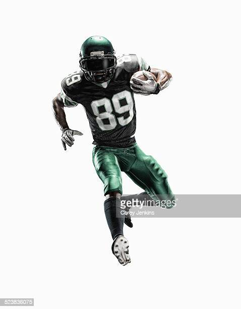 studio shot of young male football player running with ball - football player stock pictures, royalty-free photos & images