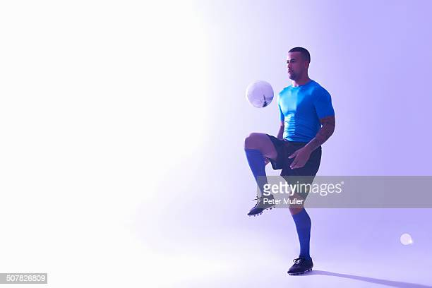 Studio shot of young male soccer player keeping ball mid air with knee