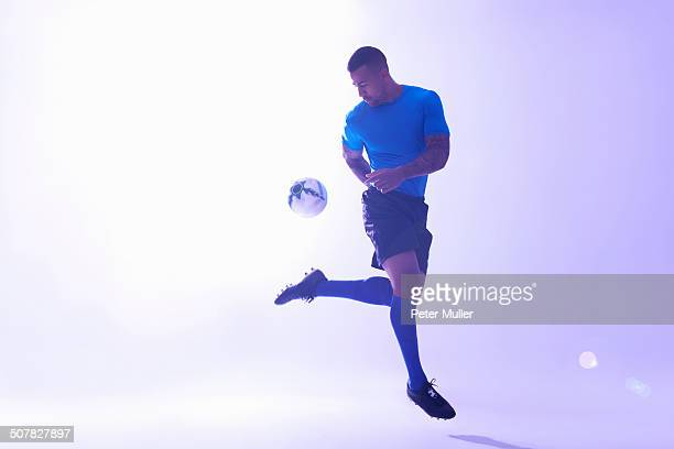 Studio shot of young male soccer player keeping ball mid air with back kick