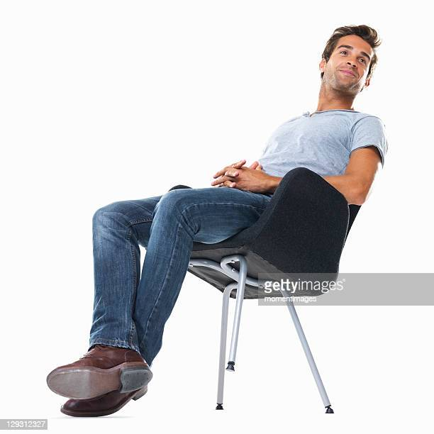 Studio shot of young man balancing on chair