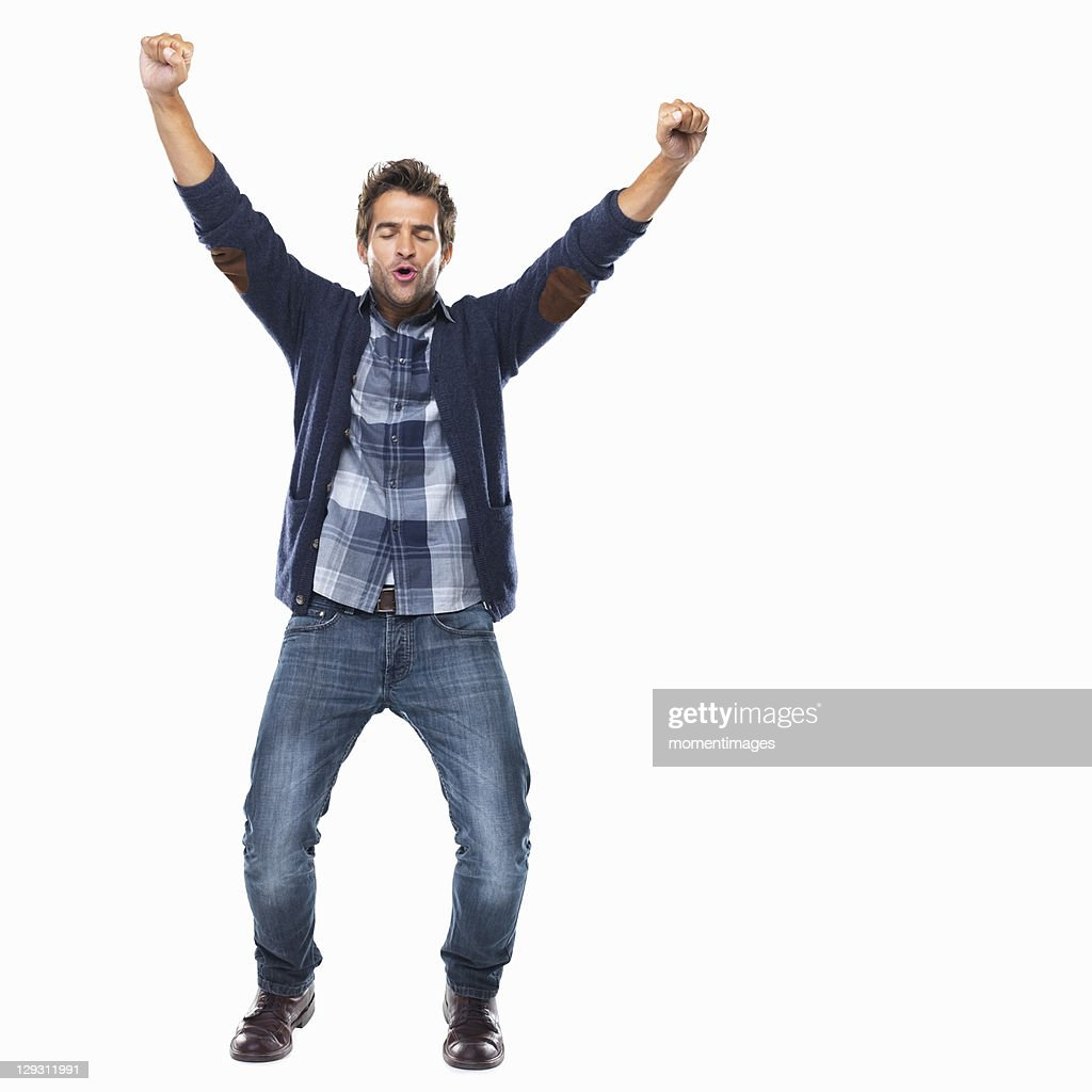 Studio shot of young man celebrating with arms raised : Stock Photo