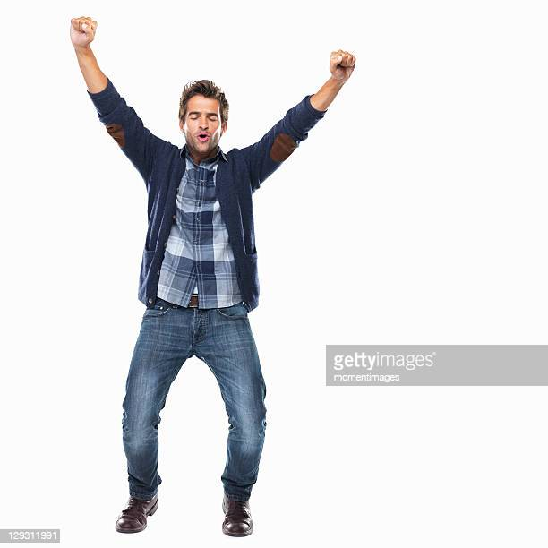 studio shot of young man celebrating with arms raised - vreugde stockfoto's en -beelden