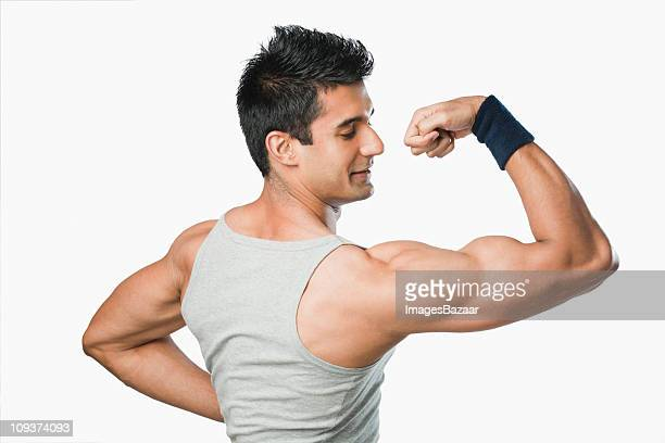 Studio shot of young man flexing muscles