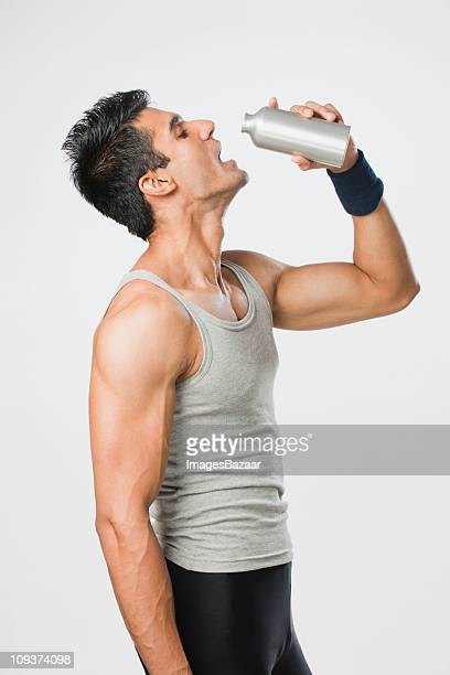 Studio shot of young man in sports clothing drinking water