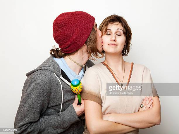 Studio Shot of young man kissing young woman