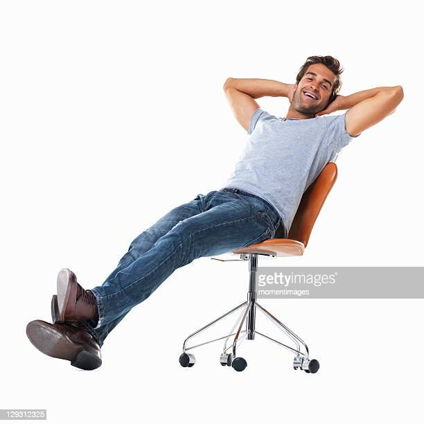 Studio shot of young man relaxing on chair