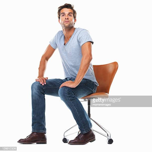 studio shot of young man sitting on chair with hands on laps - hand on knee stock pictures, royalty-free photos & images