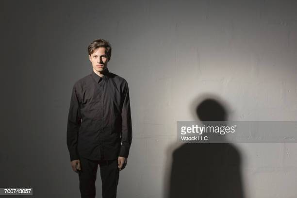 studio shot of young man wearing black clothes on grey background - zwart shirt stockfoto's en -beelden