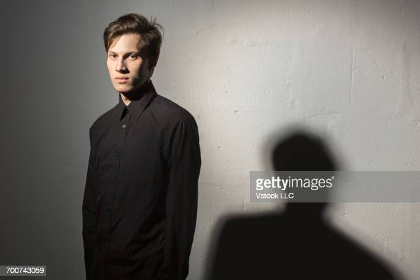 studio shot of young man wearing black clothes on grey background - 黒のシャツ ストックフォトと画像