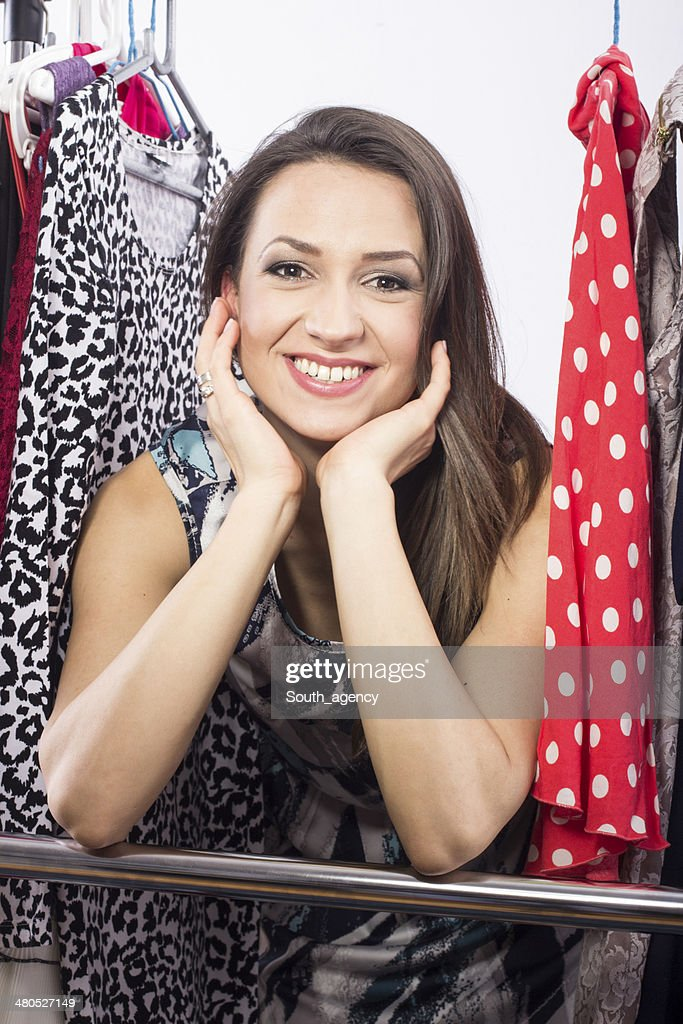 Studio shot of young model choosing dress to wear : Stockfoto