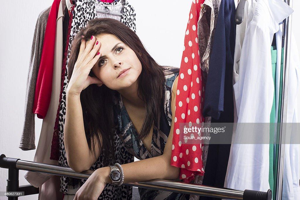 Studio shot of young model choosing dress to wear : Stock Photo
