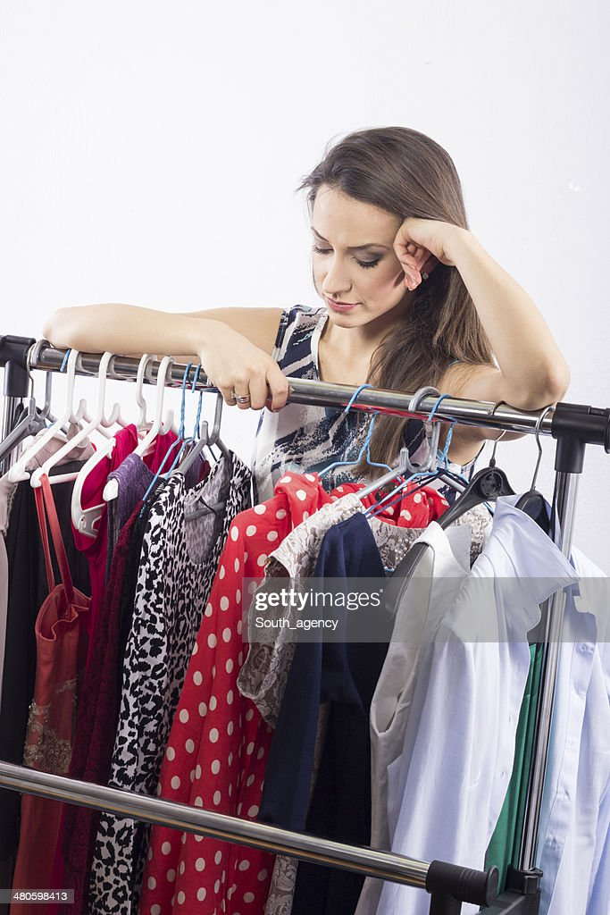 Studio shot of young model choosing dress to wear : Stock Photo