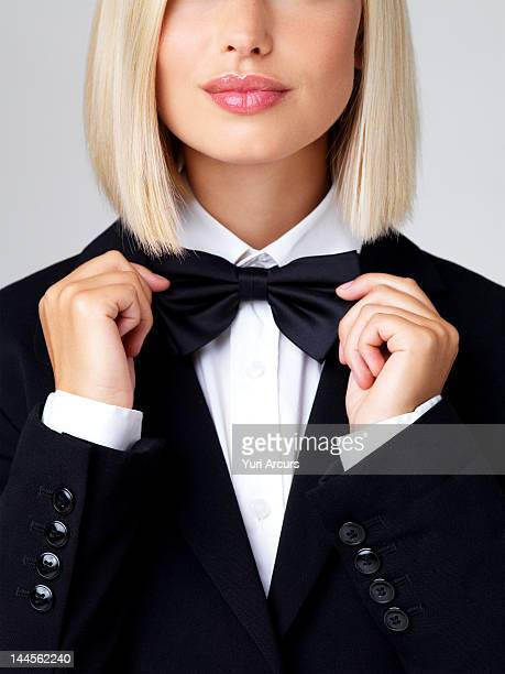 Studio shot of young waitress adjusting bow tie
