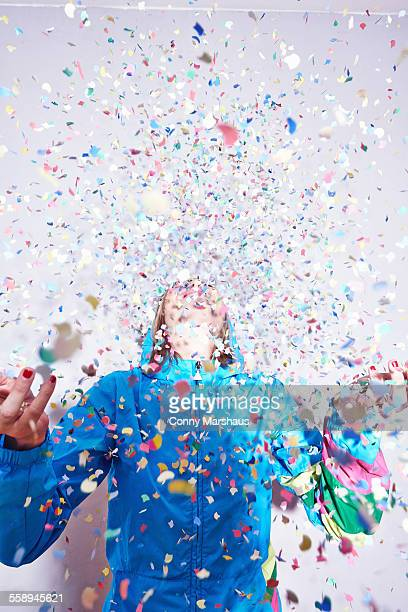 studio shot of young woman and explosion of confetti - explodieren stock-fotos und bilder
