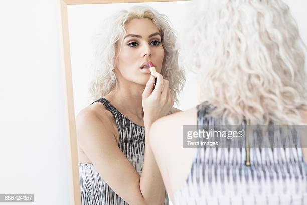 studio shot of young woman applying lipstick - transgender woman stock photos and pictures