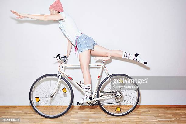 Studio shot of young woman balancing on one leg on bicycle
