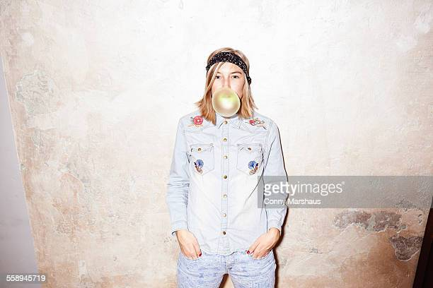Studio shot of young woman blowing yellow bubble gum bubble