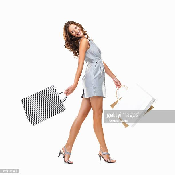 Studio shot of young woman carrying shopping bags and walking