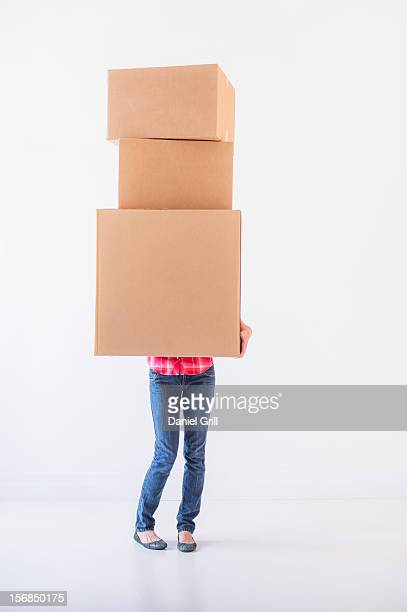Studio shot of young woman carrying stack of boxes