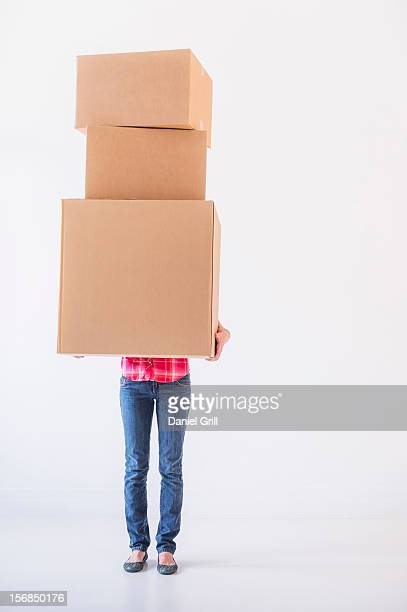 studio shot of young woman carrying stack of boxes - carrying imagens e fotografias de stock