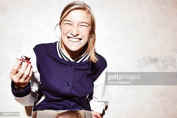 Studio shot of young woman eating chocolate marshmallows
