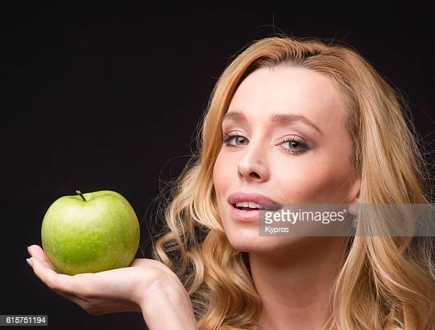 Studio Shot Of Young Woman Eating Fruit