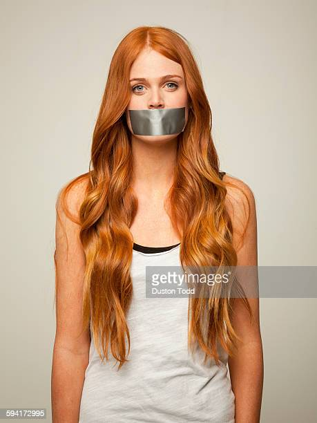 studio shot of young woman gagged with silver tape  - gagged woman stock pictures, royalty-free photos & images