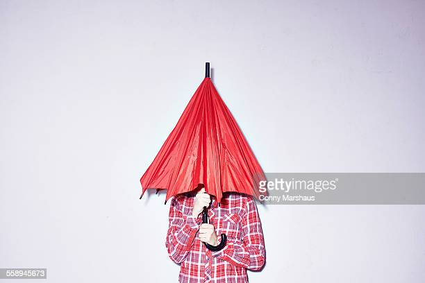 studio shot of young woman holding red umbrella over her head - verlegen stockfoto's en -beelden