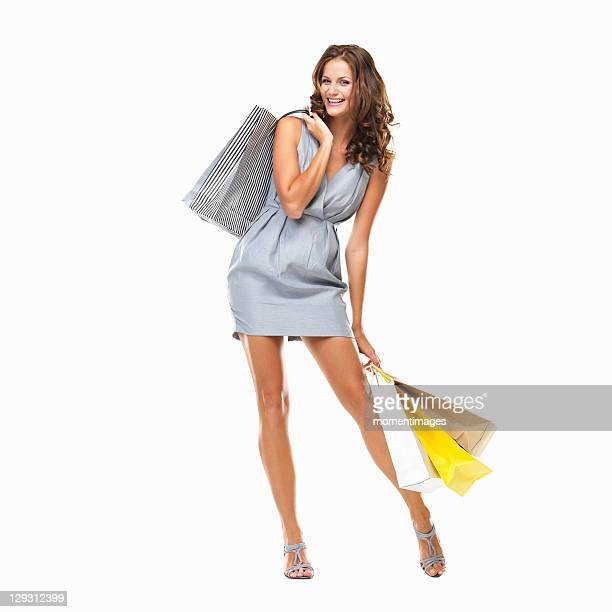 Studio shot of young woman holding shopping bags and smiling