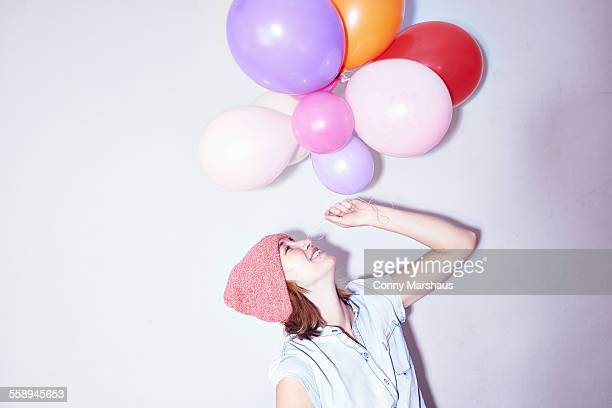 Studio shot of young woman holding up bunch of balloons