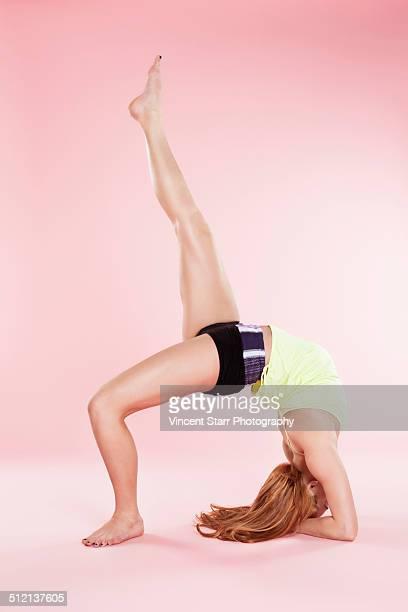 Studio shot of young woman in yoga position bending backwards with leg raised